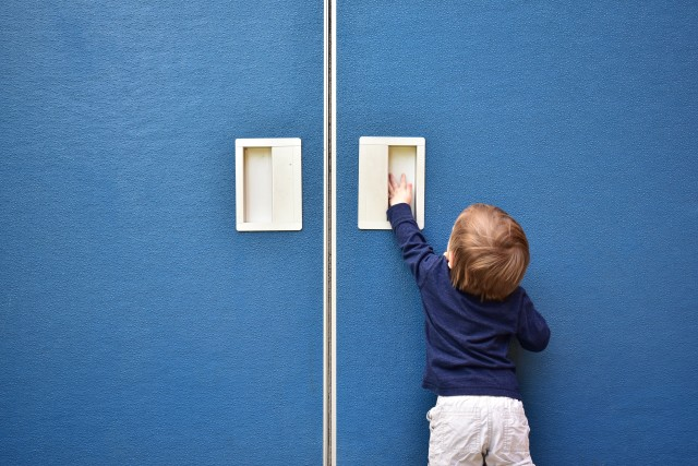 Child holding up hand to open large door